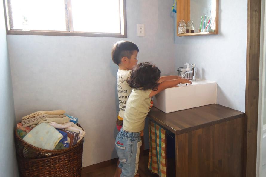 子供たちが洗面所で手を洗っています